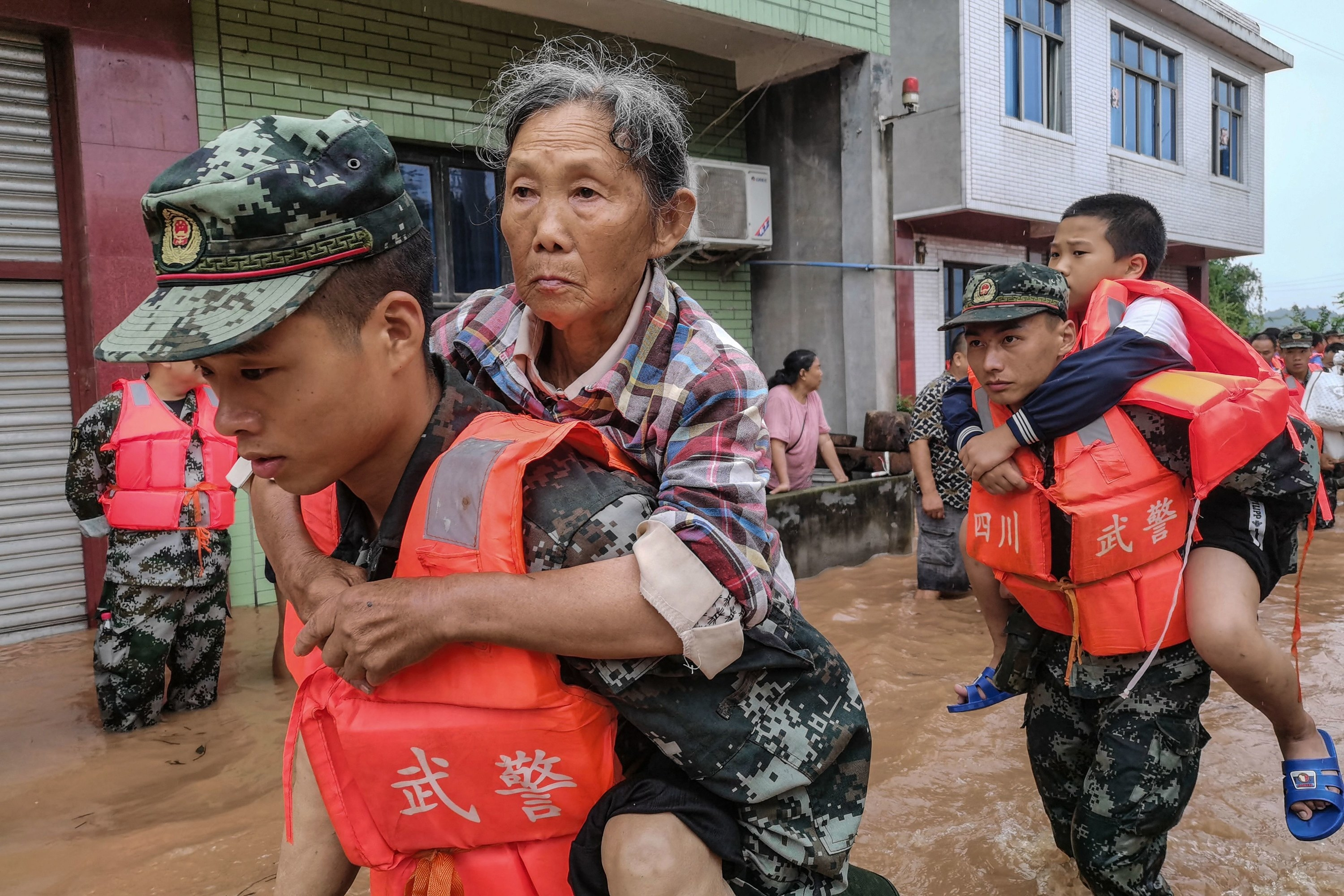 Aoliers carry an elderly woman and a boy through floodwaters
