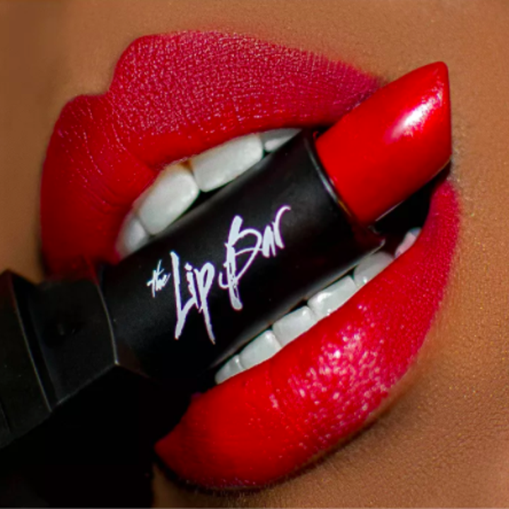 model with dark skin swatched with red The Lip Bar lipstick