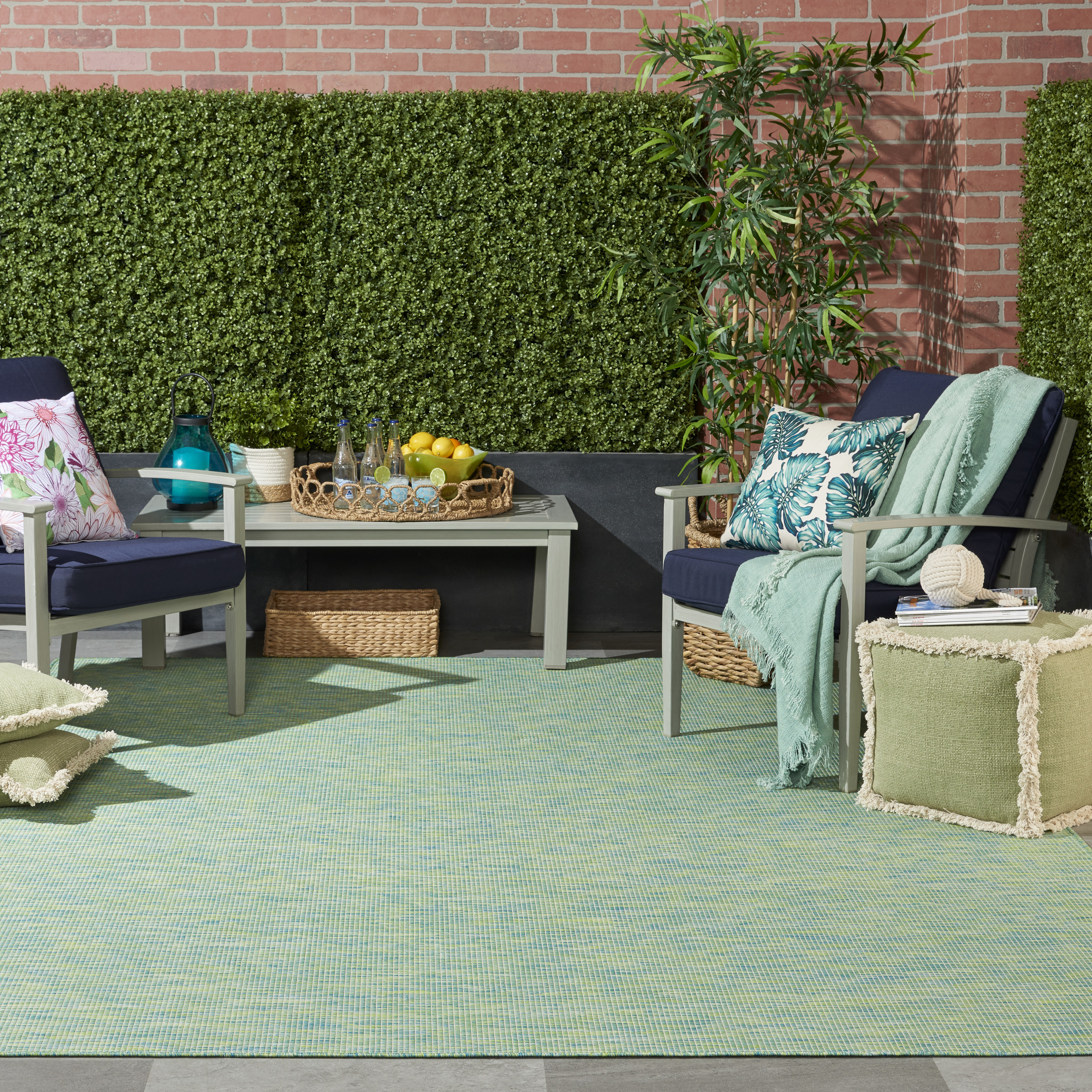 The blue/green Nourison Positano Area Rug decorating a furnished patio