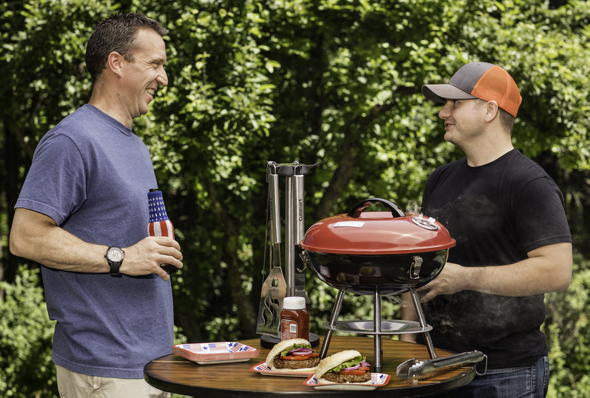 """Two models stand in a backyard in front of a table with the Cuisinart 14"""" Portable Charcoal Grill"""