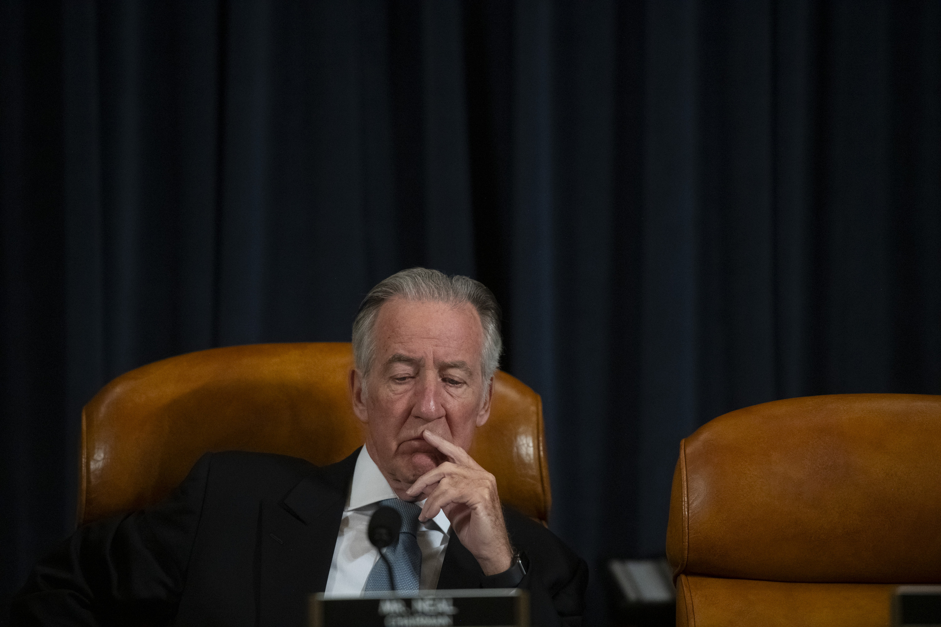 Richard Neal sits on a leather chair with his hand to his face during a congressional committee meeting