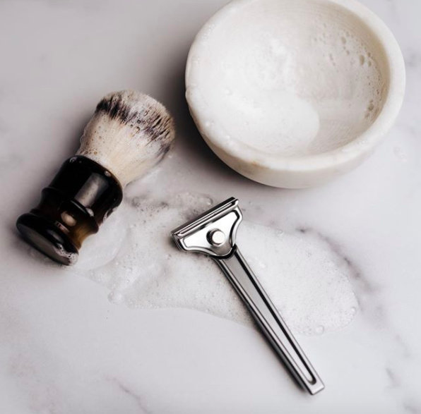 the razor with a shaving brush and marble shaving bowl