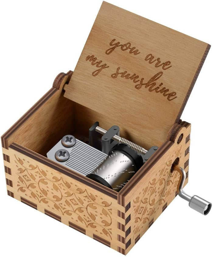 An open music box with a crank and an engraving that says you are my sunshine