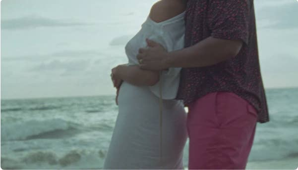Side view of John and Chrissy holding Chrissy's baby bump while overlooking the ocean