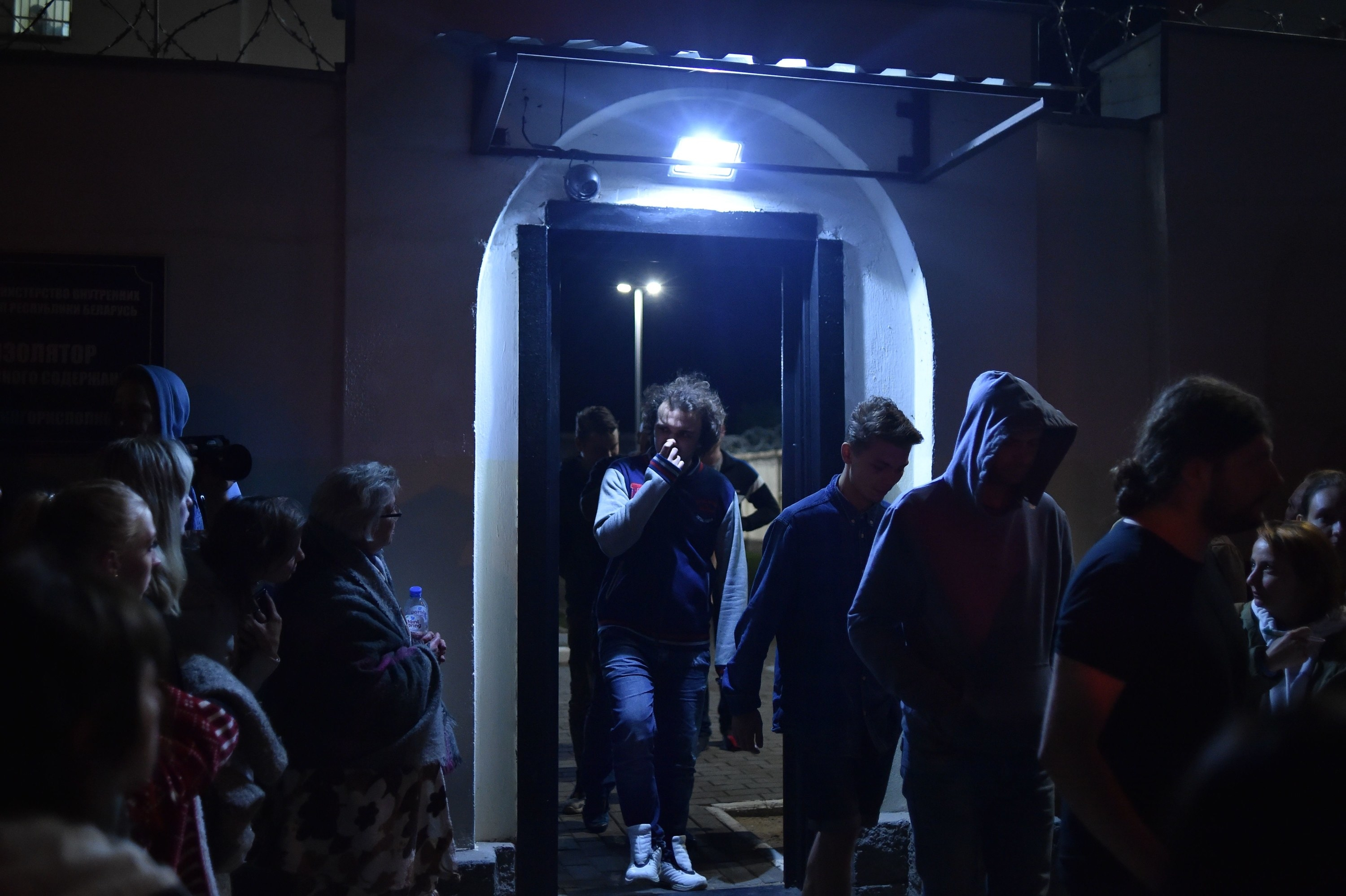 A line of people, many with their heads bowed, exit a prison doorway to crowds of people waiting outside