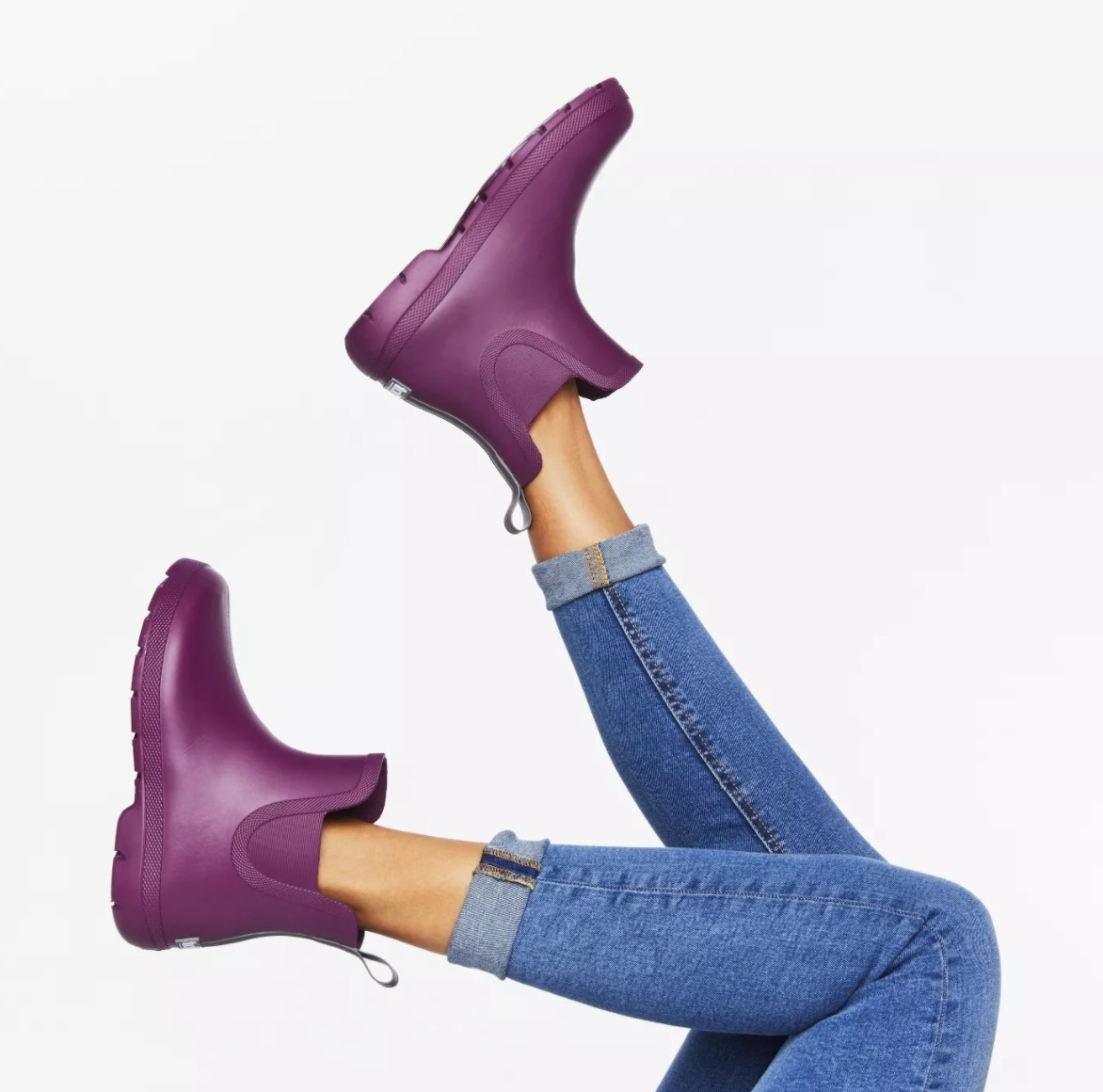 A model's legs show off a pair of ankle-length purple rubber rain boots