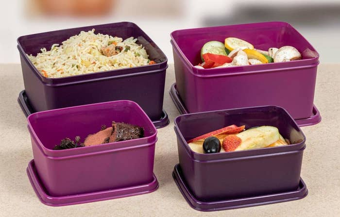Four purple containers with various food items inside them.