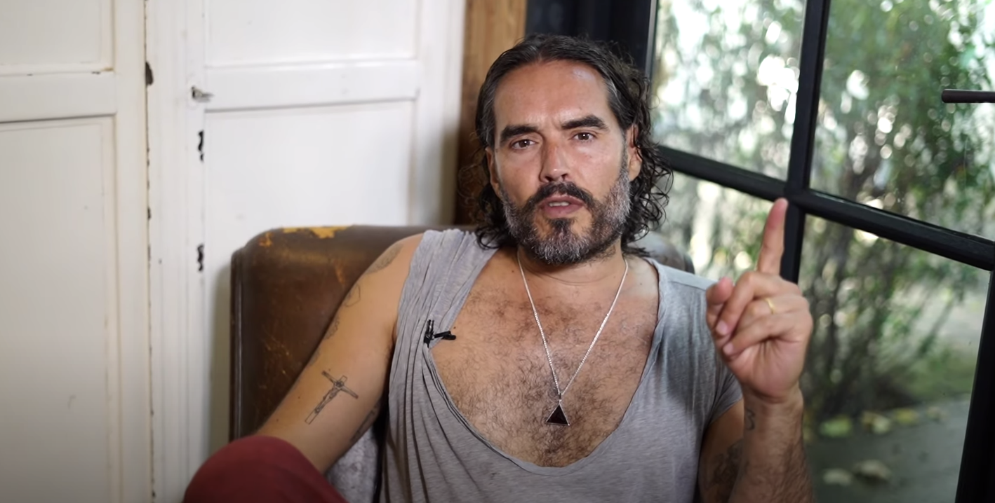 Russell Brand points his finger up while sitting in a chair at his home