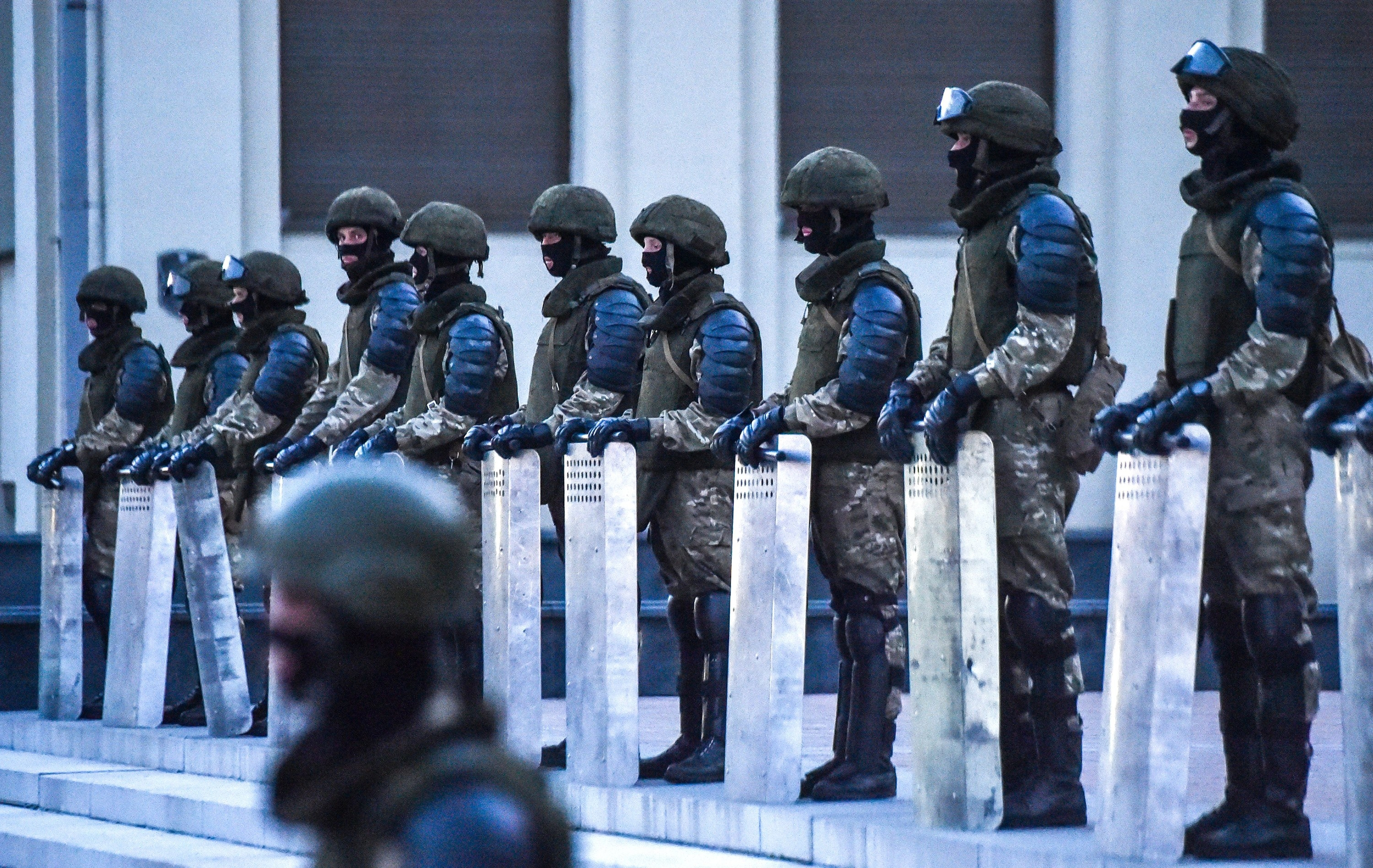 Ten officers in military gear stand in a line holding large shields
