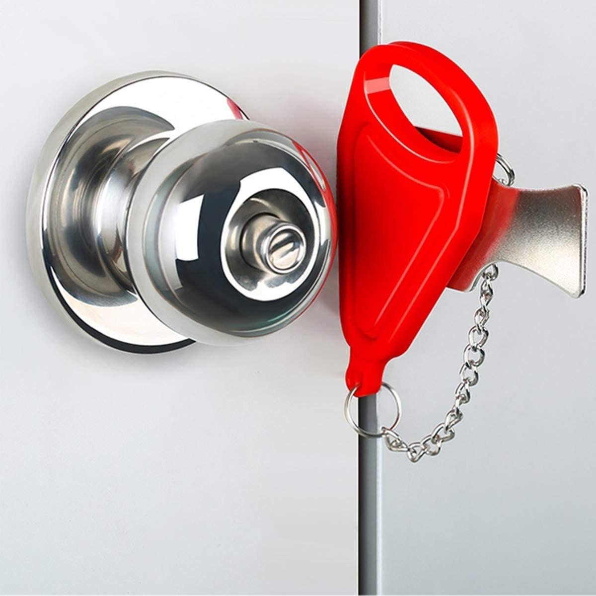 A  portable door lock wedged into a door beside the handle