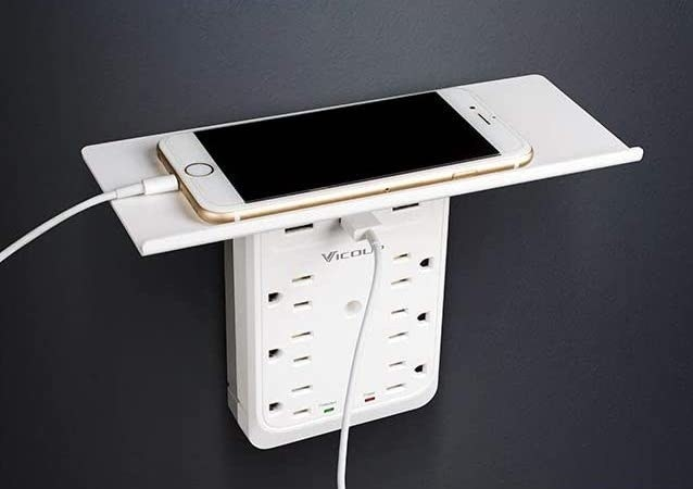 An iPhone on top of the shelf of the surge-protecting outlet