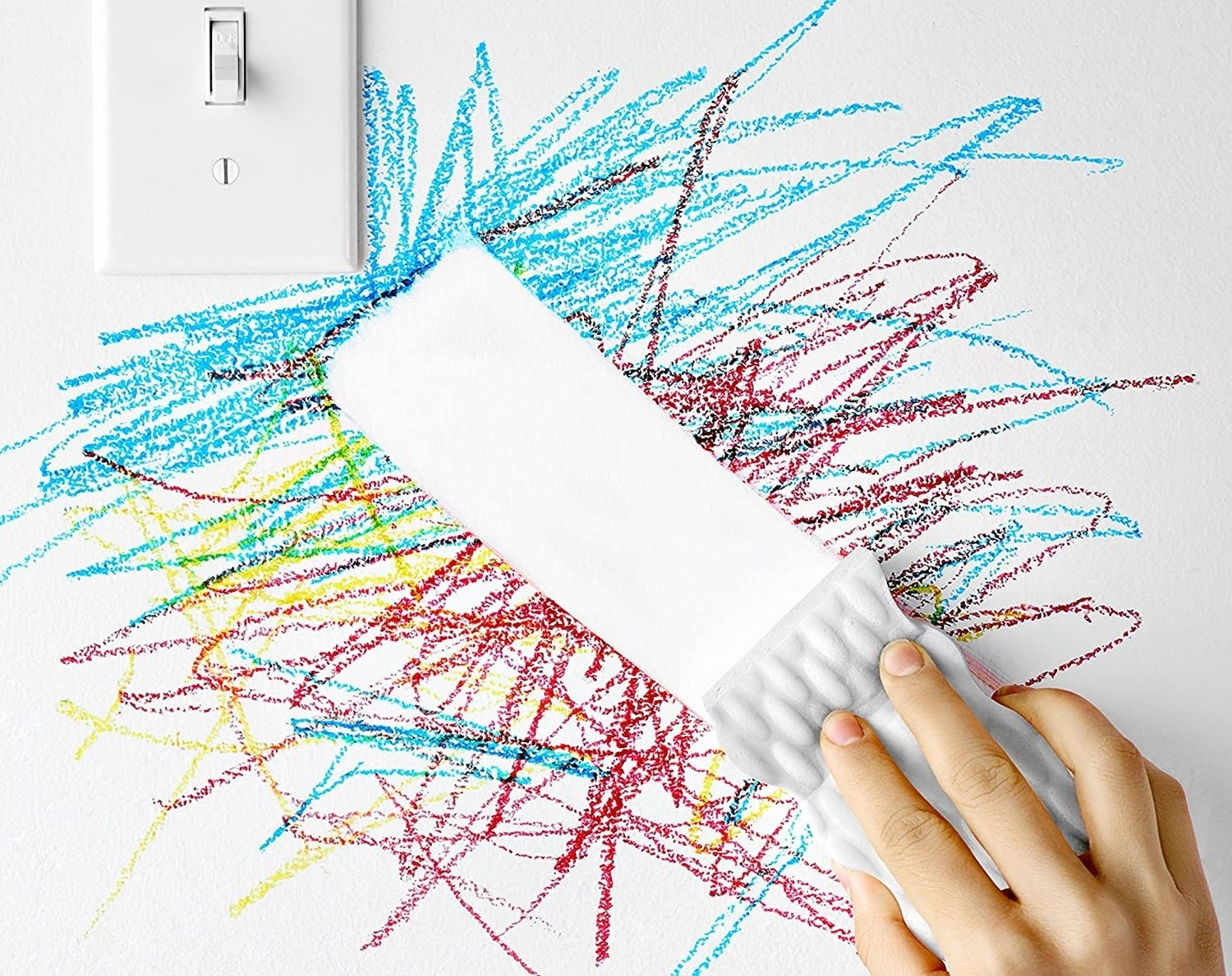 A person wiping away crayon marks on a wall with a Magic Earaser