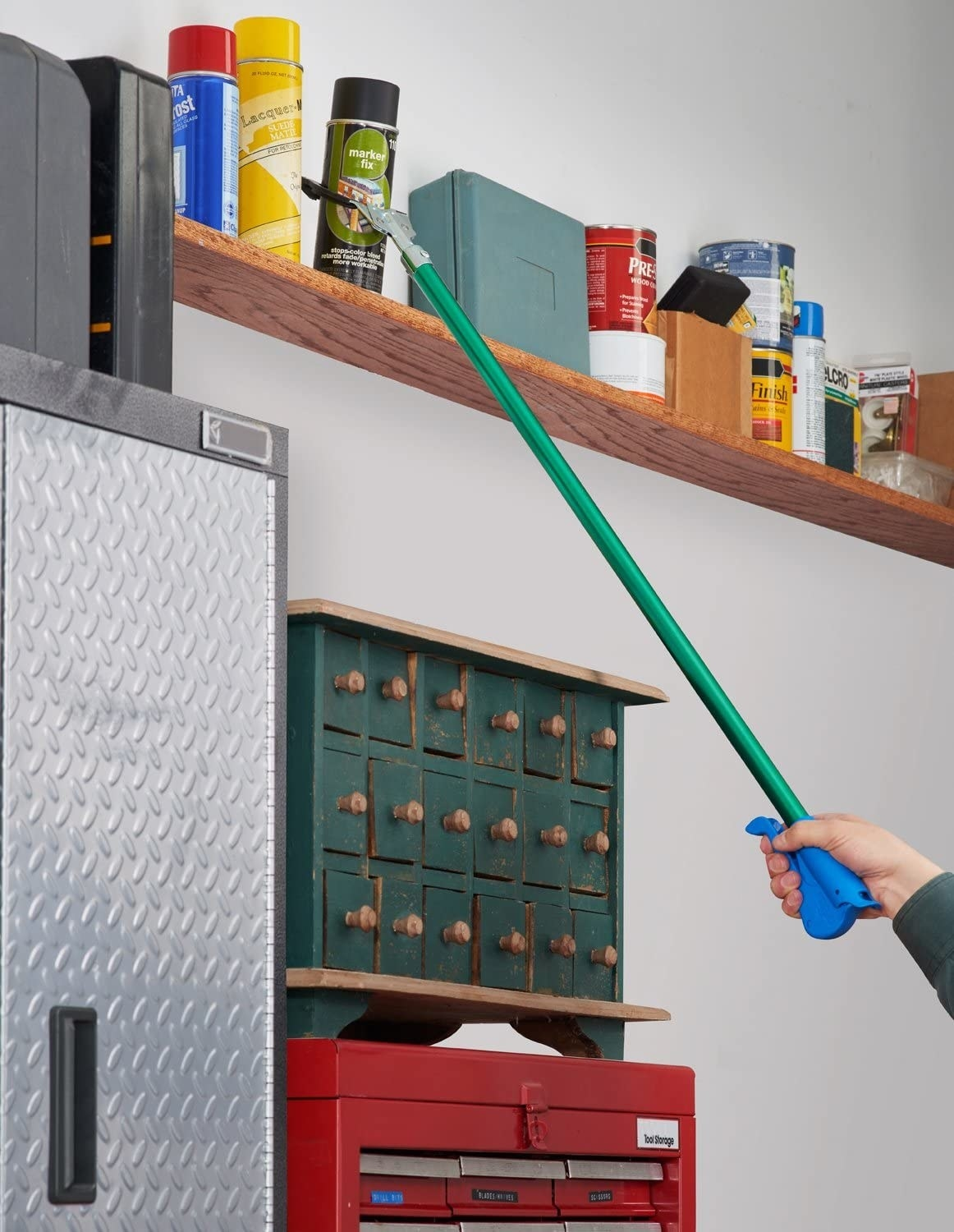 A person uses a reaching tool to grab something from a high shelf