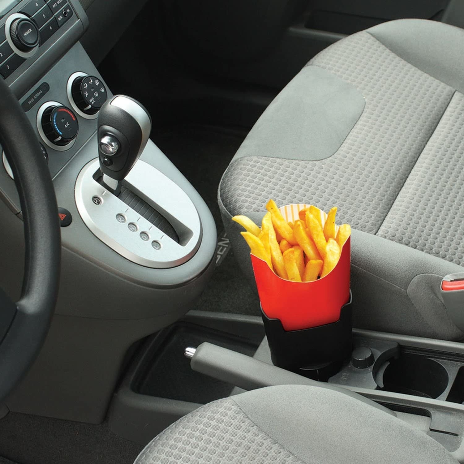 French fries stand upright in a holder fitted into a car's drink holder