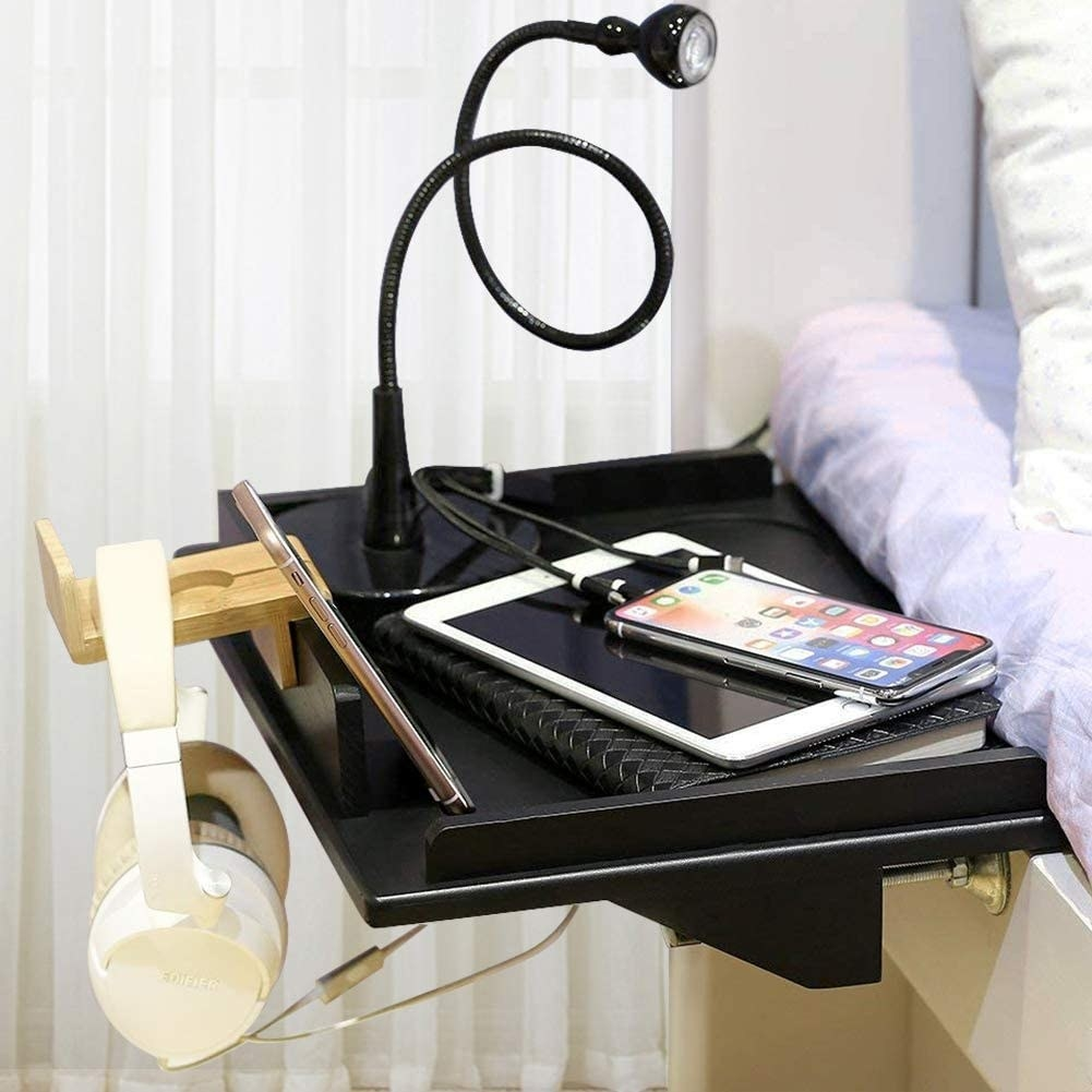 A book, tablet, cellphone and light on top of a bedside shelf