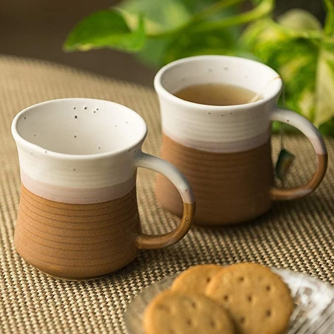 White and brown ceramic mugs with handles.