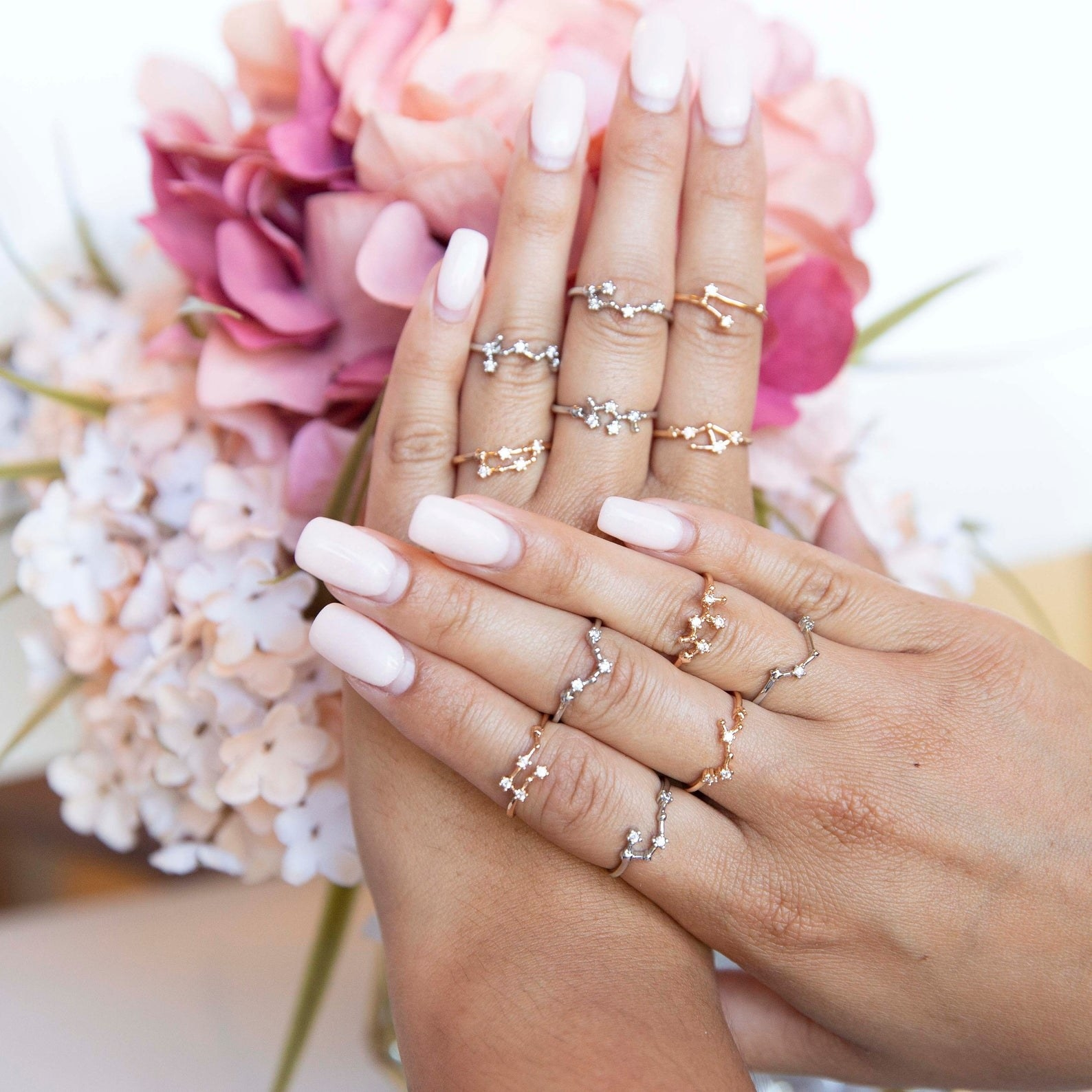 Model's hands with assorted zodiac sign rings in gold in silver on each finger