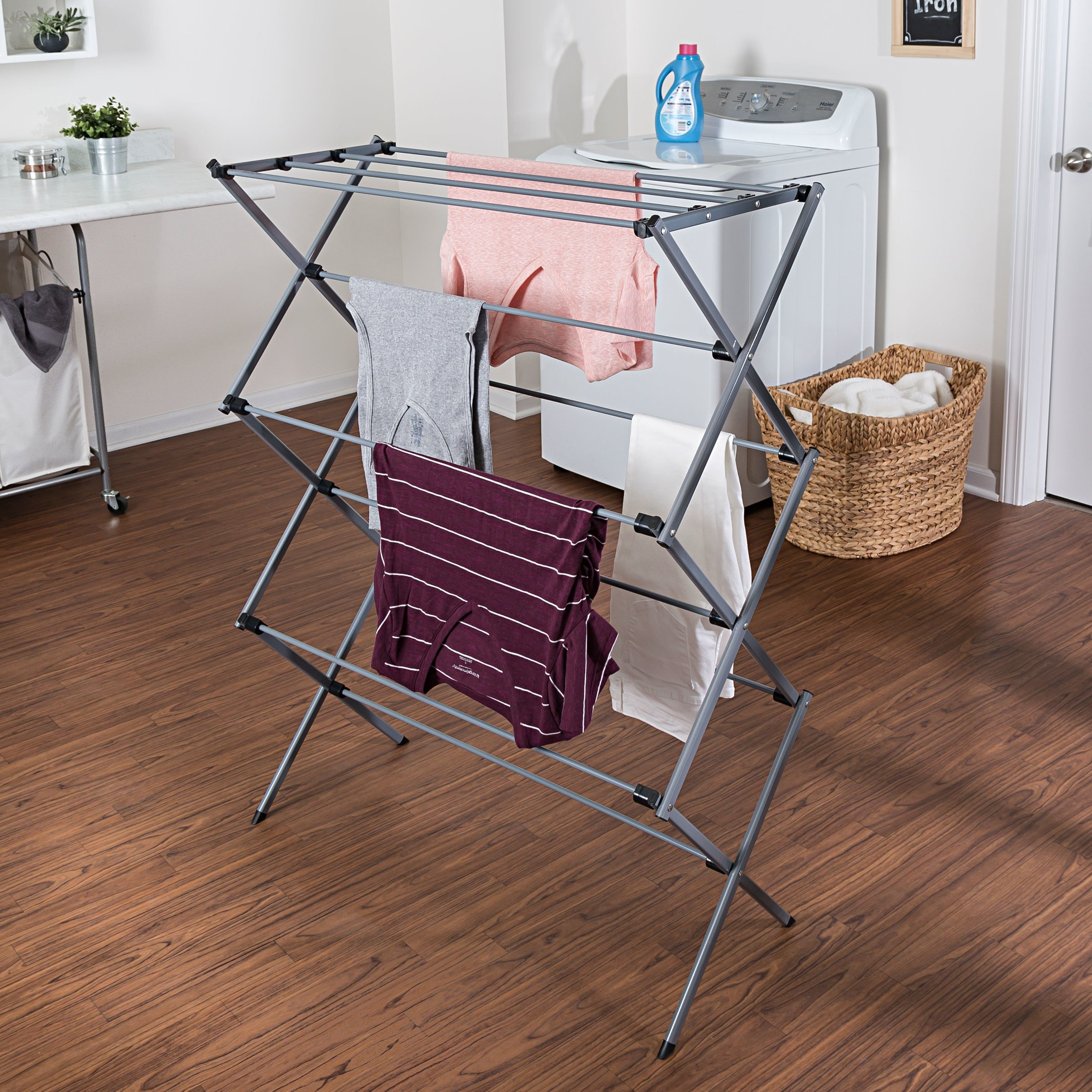 A gray plastic laundry drying rack with clothes on it