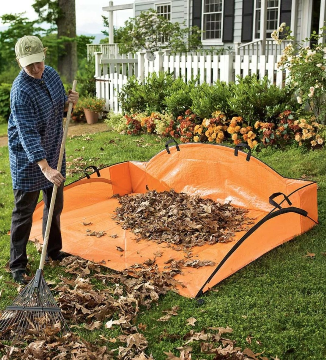 A model using an orange tarp with handles for leaves