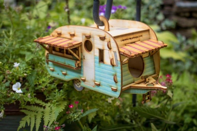 Wood birdhouse that looks like an old camper that's half teal and half white with an awning on the front and side