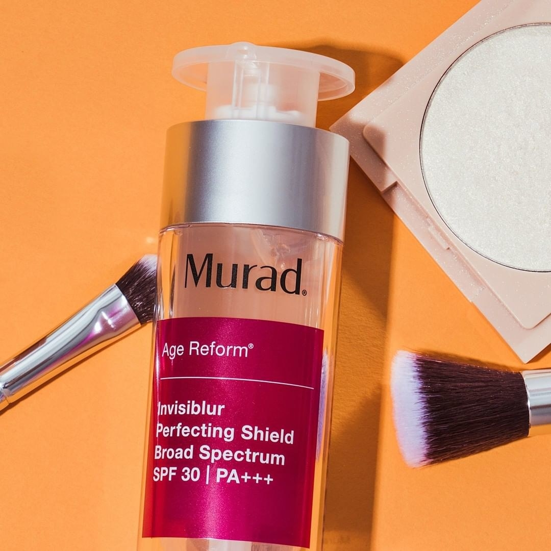 The perfecting shield bottle with two makeup brashes and a blush around it