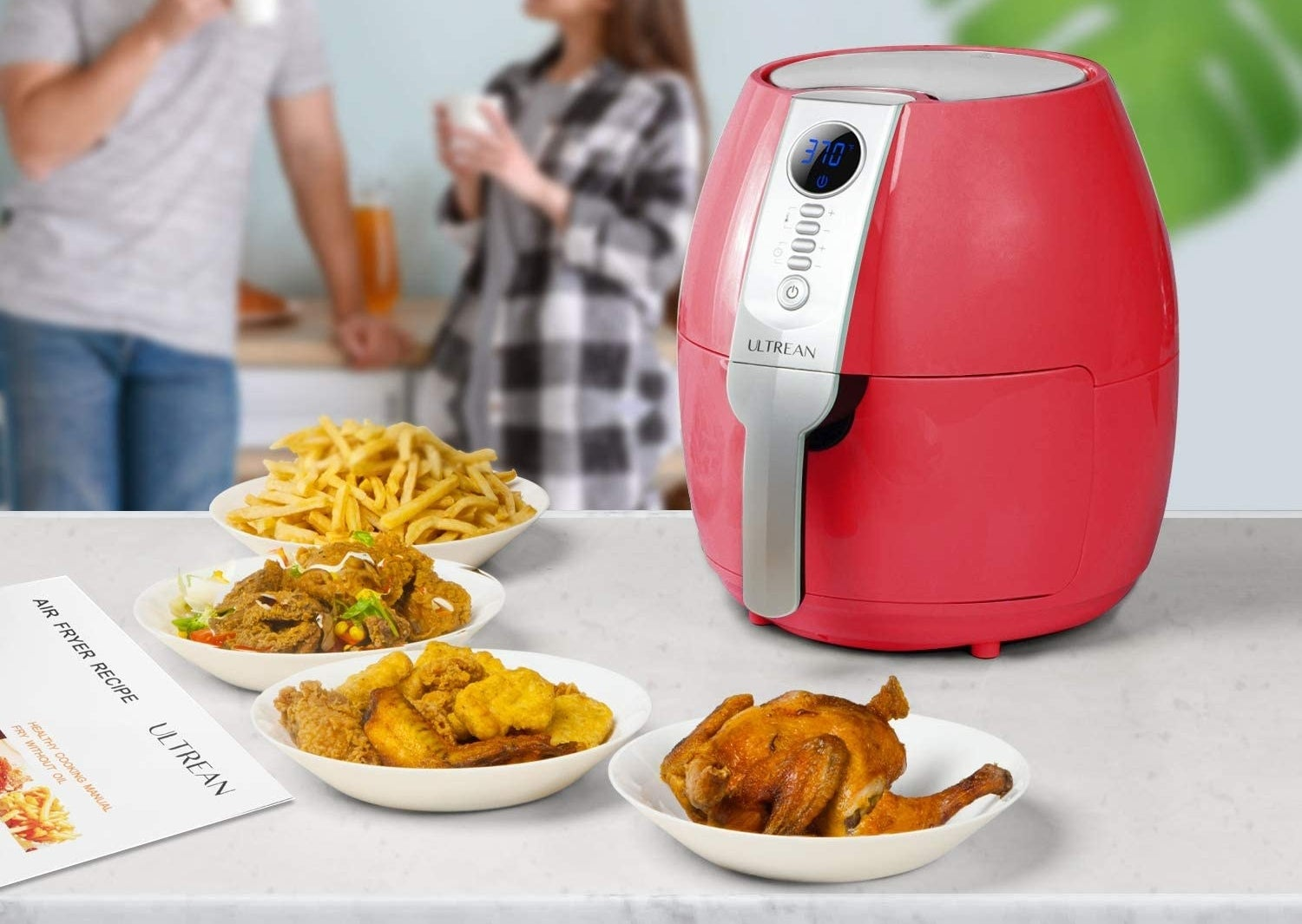 The red air fryer on a counter next to plates of fries, chicken, and other foods