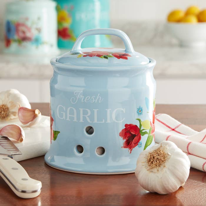 Product photo showing 5.7 inch garlic keeper storage container by The Pioneer Woman in baby blue with decorative flowers