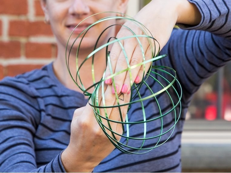Model playing with the spherical-shaped spiral toy between their hands