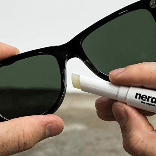 person putting nerdwax on the bridge of sunglasses