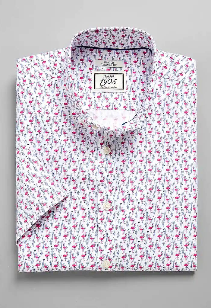 A folded white collared short-sleeve shirt with a bright pink flamingo pattern