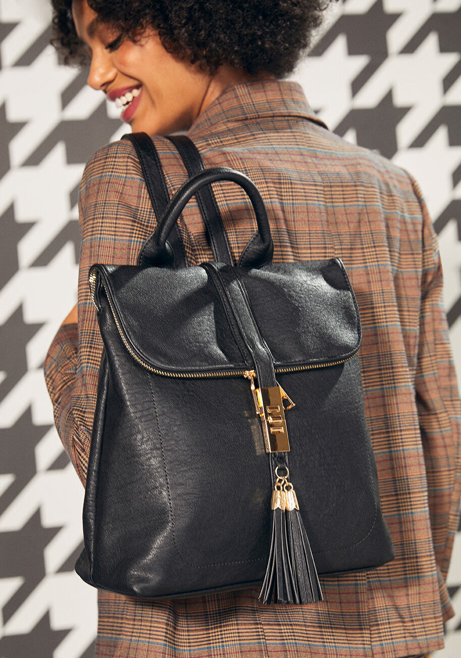 The black backpack around a model's shoulders. It has gold metal details, two tassels on the buckle, a zipper, a top handle, and back straps.