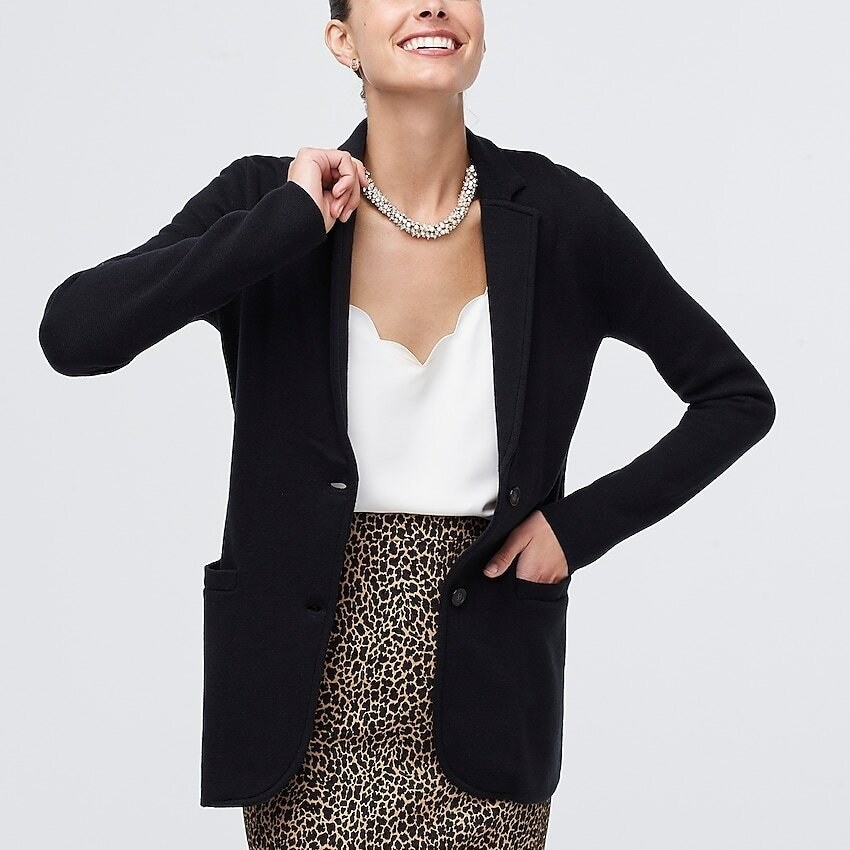 A model wearing the blazer shaped sweater with a cami and pencil skirt. It has two front buttons and two pockets.