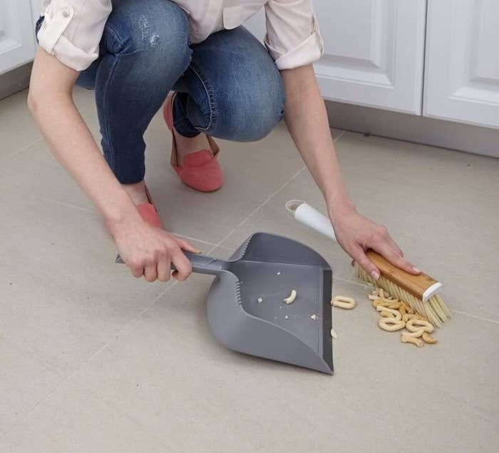 A model sweeps spilled food into the dustpan