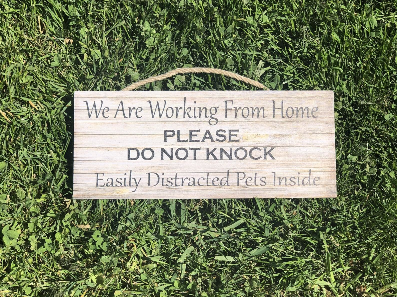"Wooden sign that says ""We are working from home, please do not knock, easily distracted pets inside"""