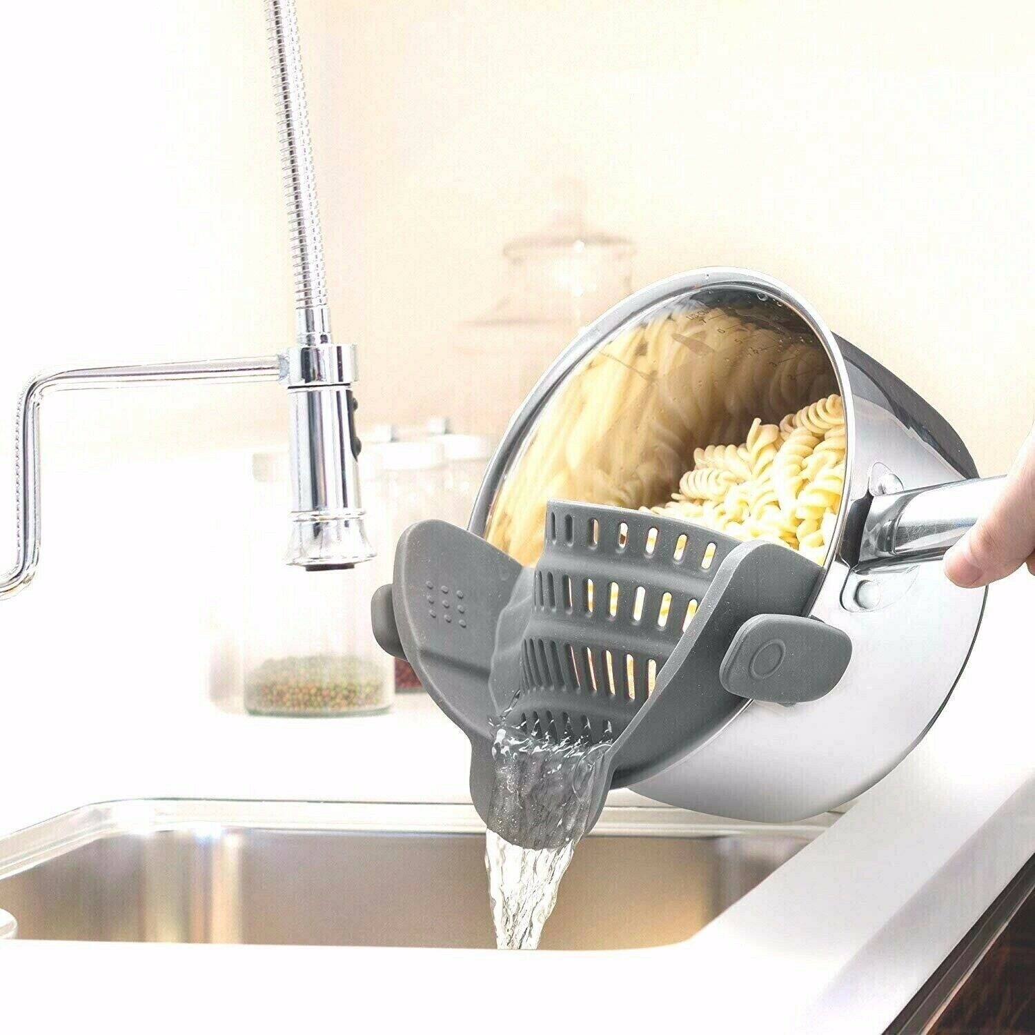 Product photo showing Snap N Strain clip on silicone strainer being used to strain cooked pasta