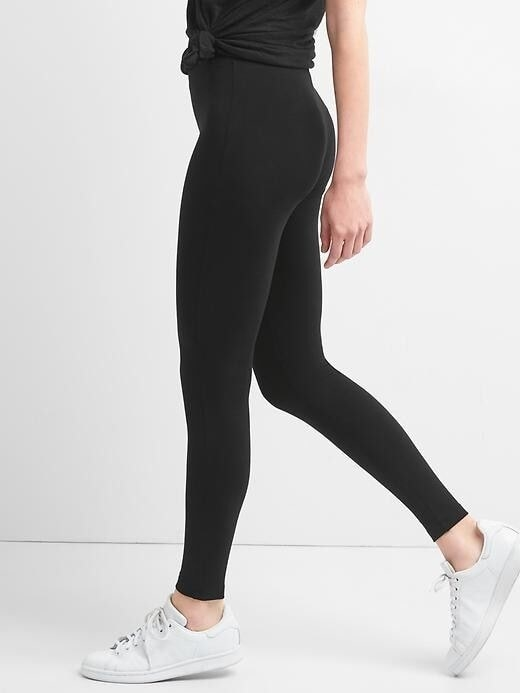 A person wearing the leggings with tennis shoes. They hit right at the ankle and ride above the hip bones.