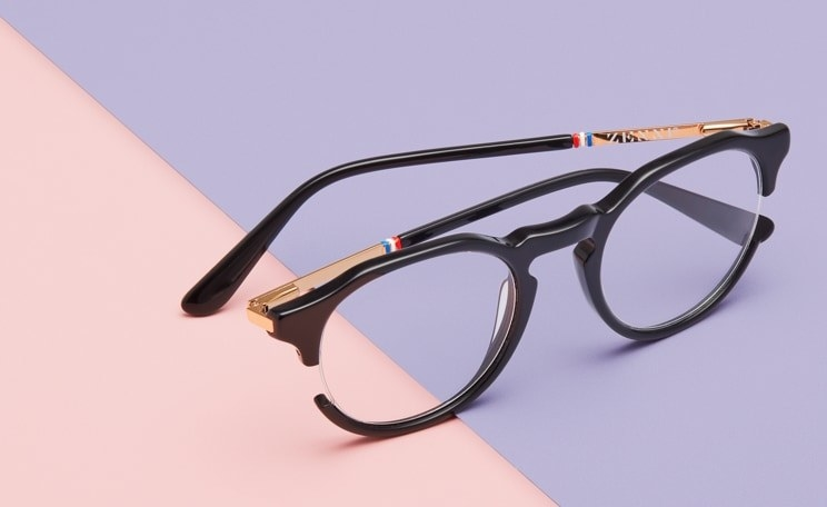 A pair of black glasses with rounded frames that curve naturally at the top. The legs are gold and the frame cuts off on the side of each lens, giving them a clear sided detail.