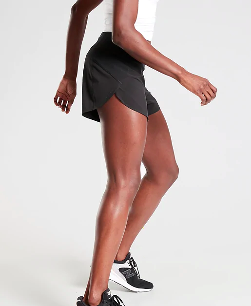 A woman wearing black Athleta running shorts and running sneakers.