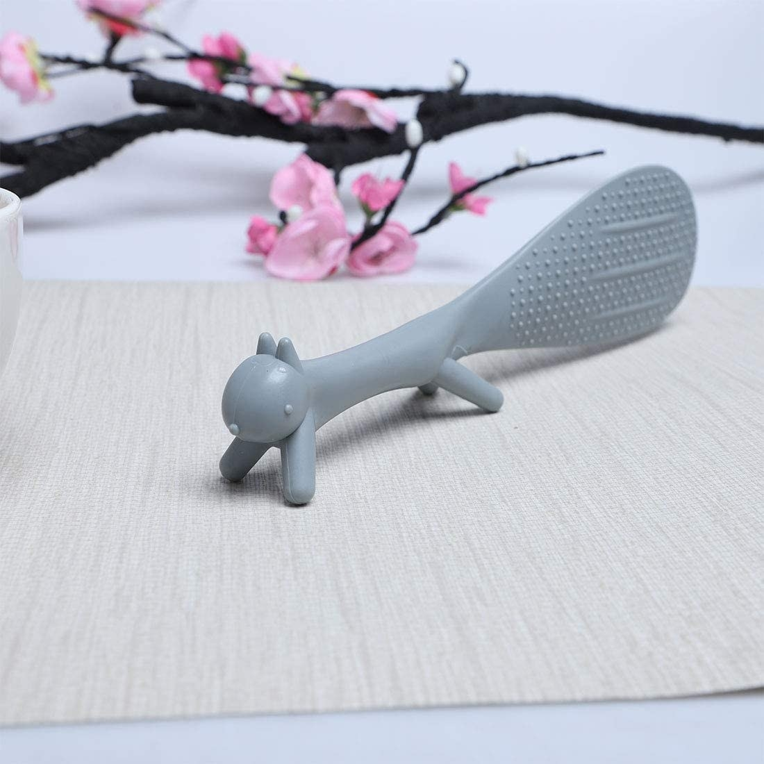 A close up of the squirrel shaped rice scoop placed neatly on a tabletop