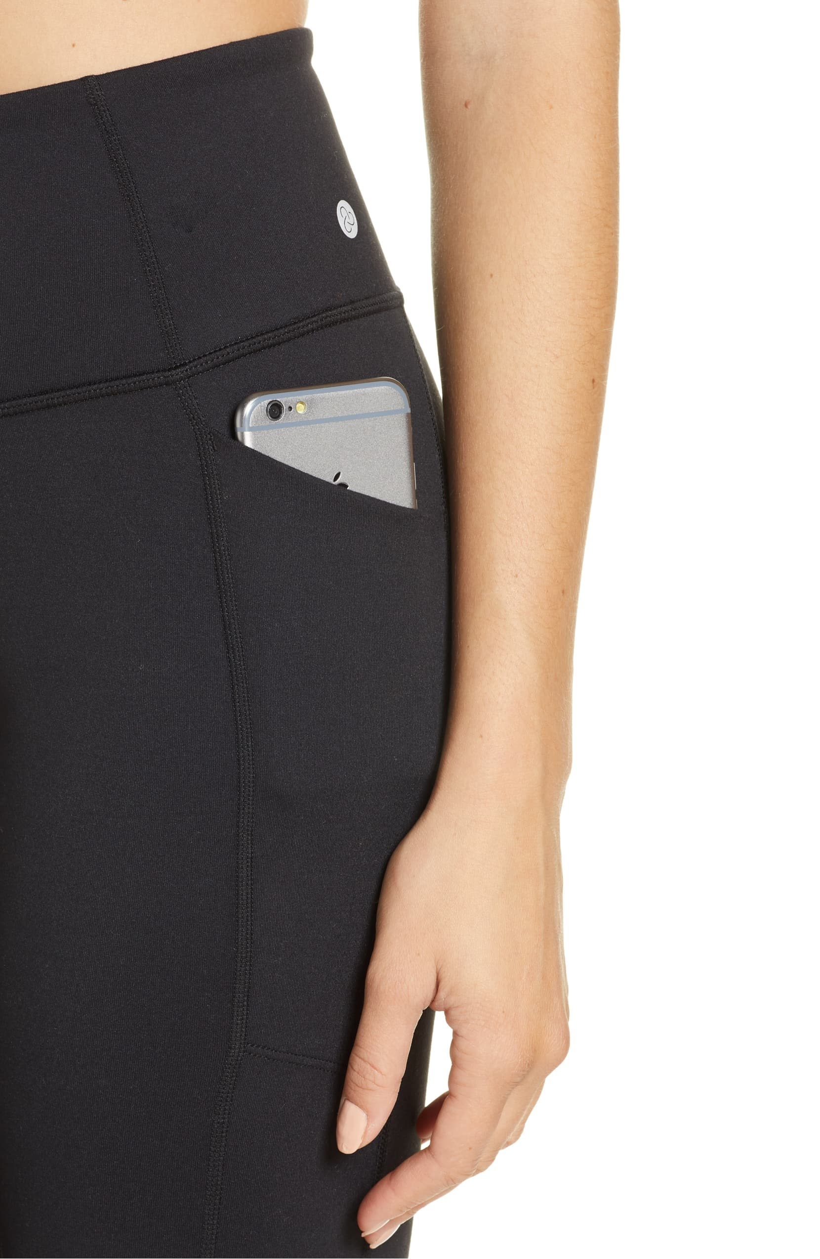 A woman wearing Zella leggings with a phone in the side pocket.