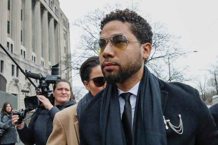 Jussie Smollett walking outside a courthouse with reporters behind him