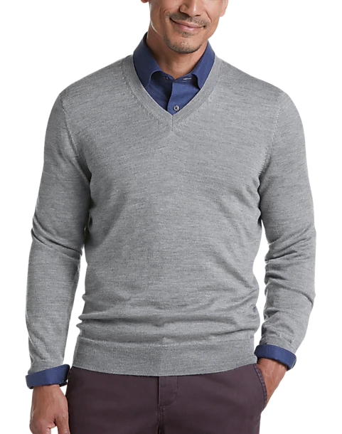 Model wearing a light gray v-neck sweater with plum pants and dark blue shirt