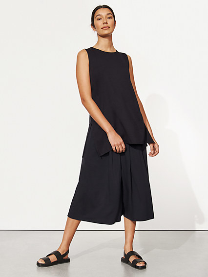 The loose fit, flowing tunic paired with flowing pants. It has a high neckline, is sleeveless, and has two slits up the side raised to the hip bone.