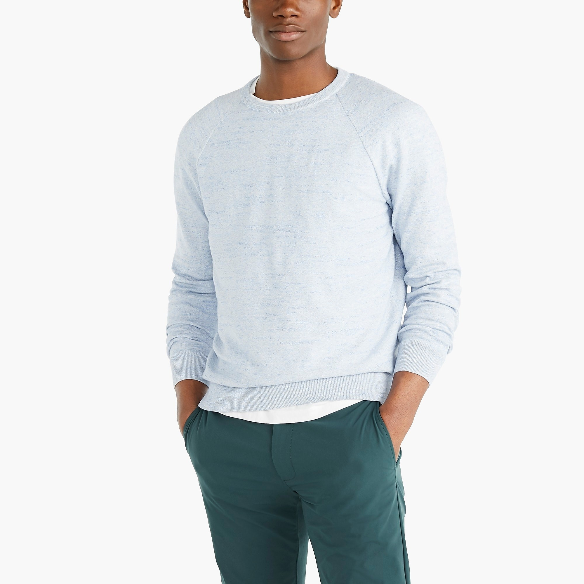 Model wearing heather sky-colored crewneck sweater over green pants