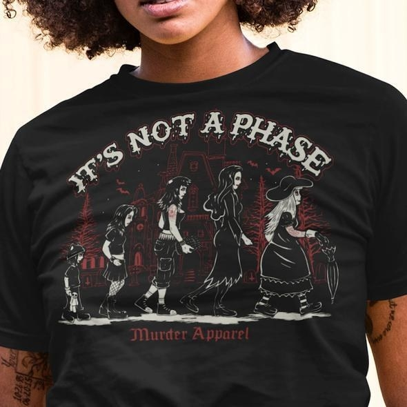 "A tee with a graphic of a person as a child, teenager, adult, and senior wearing a different style of goth attire for each stage of life. The words ""It's not a phase"" are written above the image."