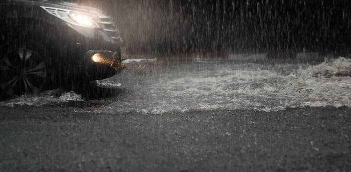A car with its headlights on and rain pouring down