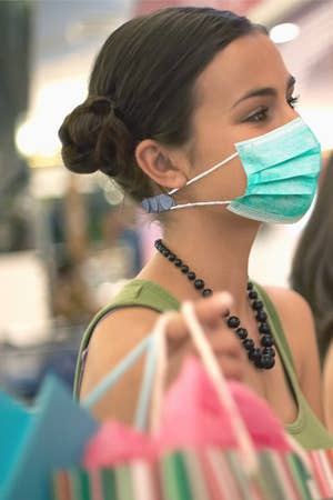 Model wearing the mask strap extender in grey on the back of their neck with a disposable mask attached to it