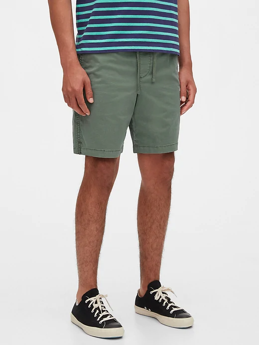 Model wearing olive green shorts with drawstring that hit above the knee