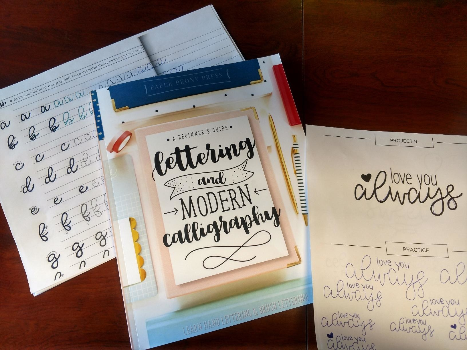 """Reviewer pic of the lettering book with a worksheet behind it to practice writing letter and another sheet on top with a project to write """"love you always"""""""