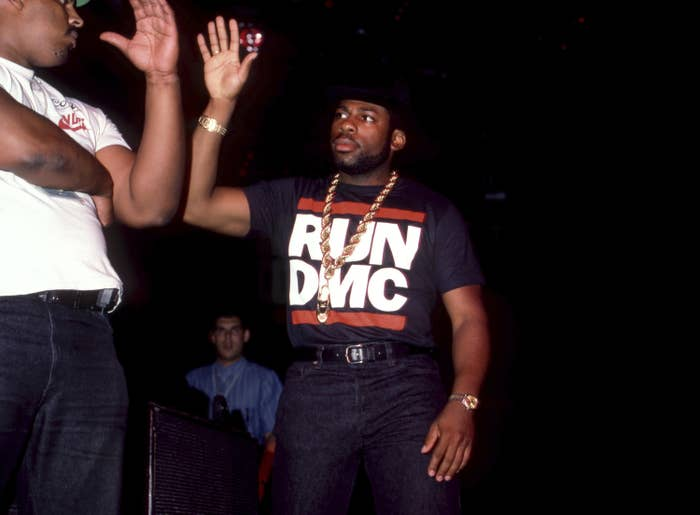 "Jam Master Jay wears a thick gold chain and a T-shirt that reads ""Run DMC"" as he gives another man a high-five"